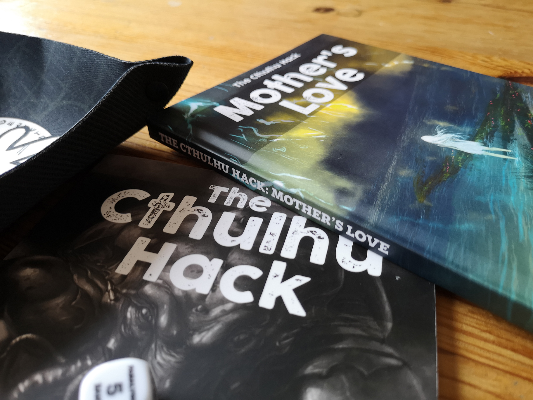 Promoting hardback book release with picture of Mothers Love, The Cthulhu Hack core book and dice tray